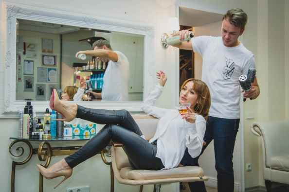 woman sitting on the salon chair while holding vodka glass and man at her back white spraying her hair